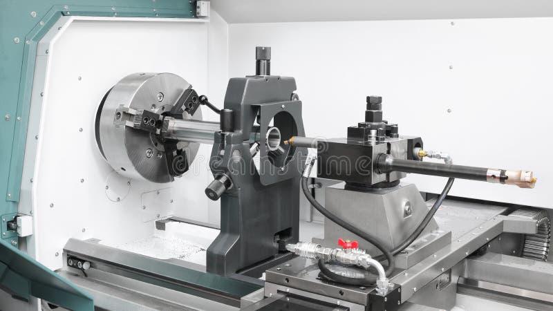 Industria metallurgica di CNC: taglio dell'asse d'acciaio del metallo che elabora sulla macchina del tornio in officina fotografie stock