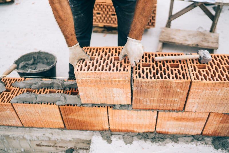 industria - primo piano delle mani dei muratori che tengono i mattoni e che installano le pareti fotografia stock