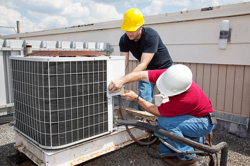 Industrial Air Conditioning Repair. Two workers on the roof of a building working on the air conditioning unit royalty free stock photography