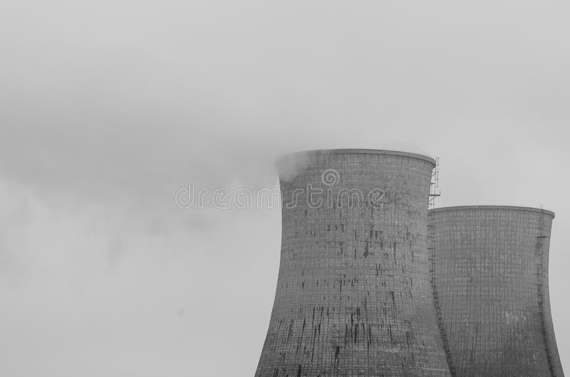 Industrial area. Refinery cooling towers covered by fog stock images
