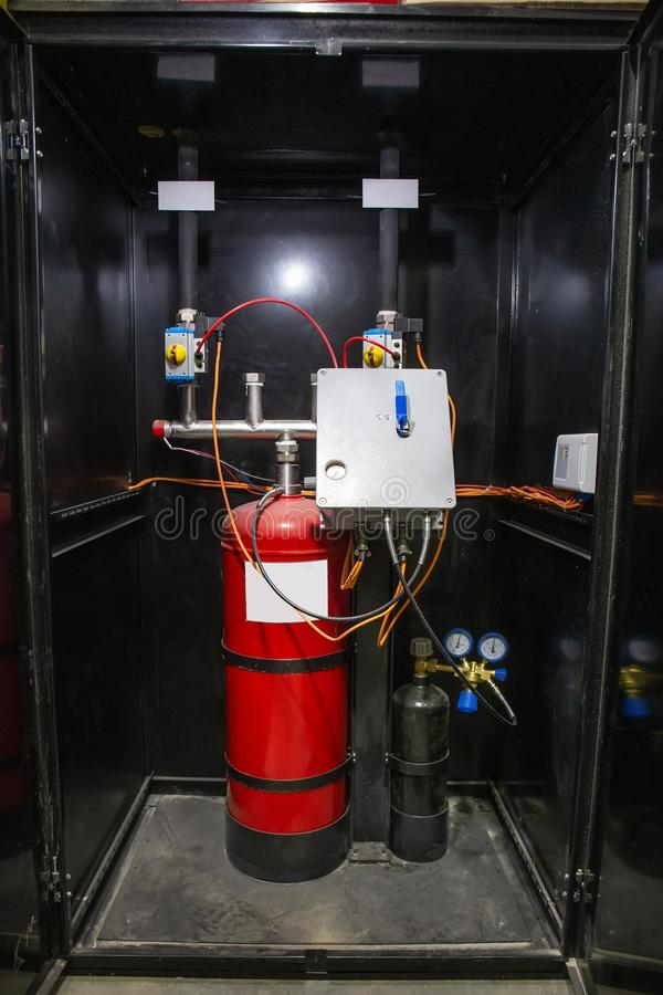 Industrial automatic fire extinguishing system, cabinet with balloon of fire-fighting foam, nitrogen and control unit. Close-up stock image