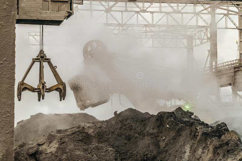 Industrial background. Loading equipment in hot dust of heavy metallurgical industry. Excavator and grapple grab of overhead crane in a dirty outdoors stock photography