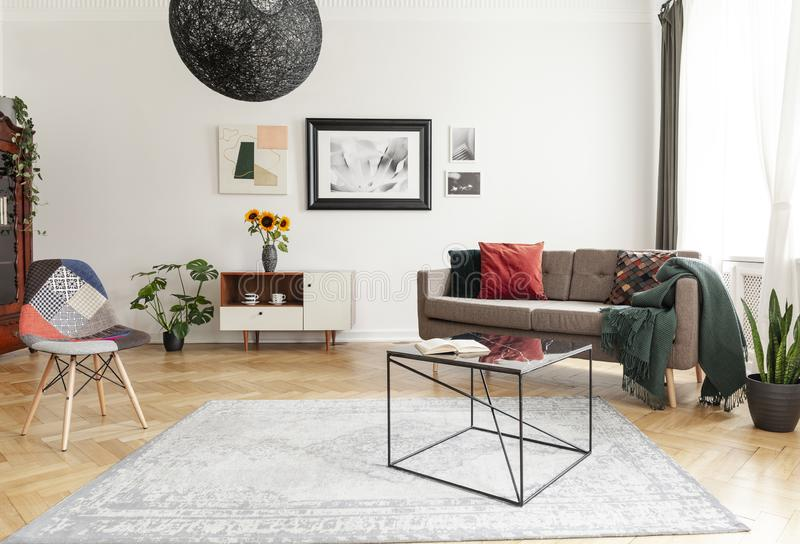 Industrial black coffee table with marble surface and a colorful patchwork chair in a living room interior with mixed style of dec. Or. concept royalty free stock image
