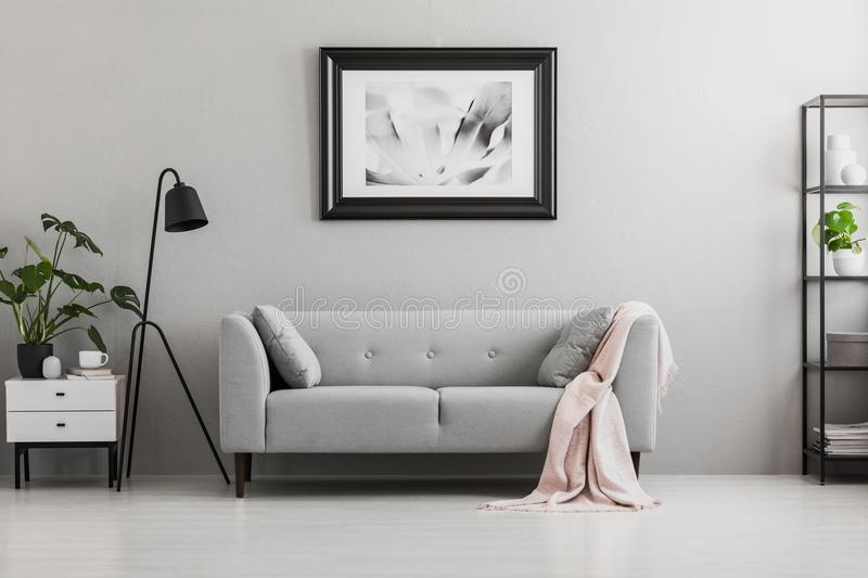 Industrial black floor lamp and a pink blanket on an elegant settee with cushions in a gray living room interior with place for a. Coffee table. Real photo stock photo
