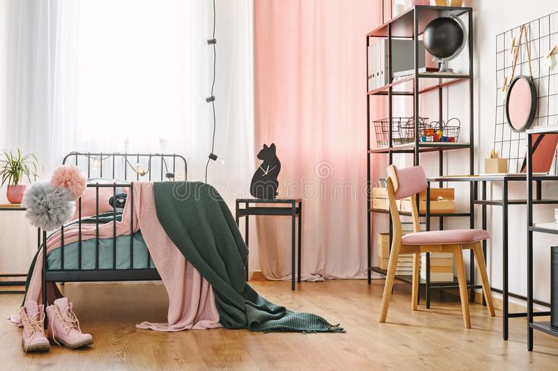 Industrial black furniture in bedroom. Industrial black furniture and cute pink textiles in a teenage student`s modern bedroom interior with cozy metal frame bed royalty free stock photos