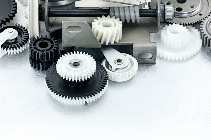 Industrial black and white plastic gears on scratched background stock images