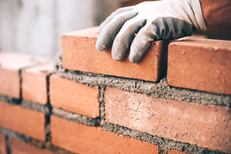 Industrial bricklayer installing bricks on construction site royalty free stock photo