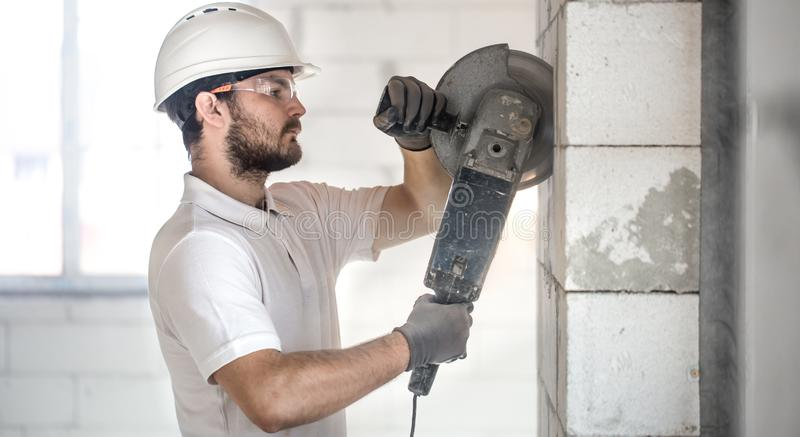 The industrial Builder works with a professional angle grinder to cut bricks and build interior walls. Electrician stock images