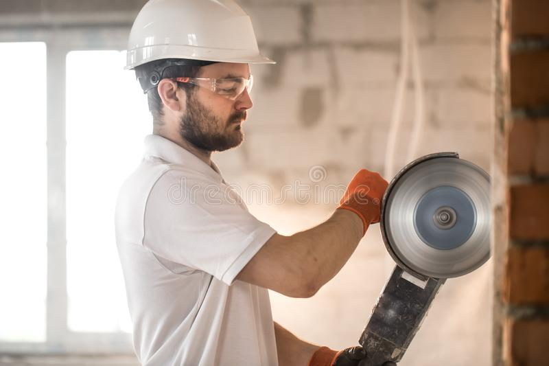 The industrial Builder works with a professional angle grinder to cut bricks and build interior walls. Electrician stock photo