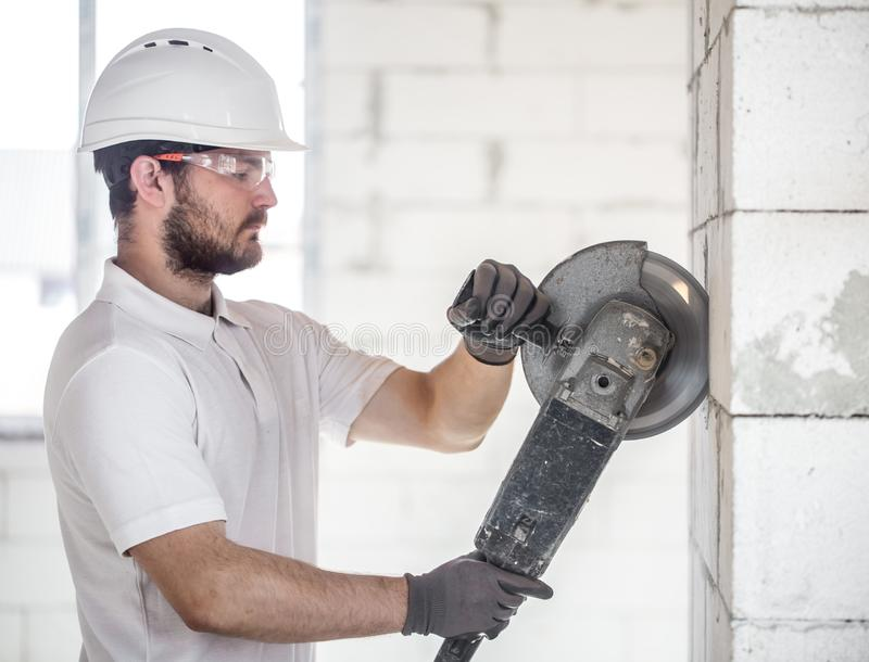 The industrial Builder works with a professional angle grinder to cut bricks and build interior walls. Electrician. The industrial Builder works with a royalty free stock photo