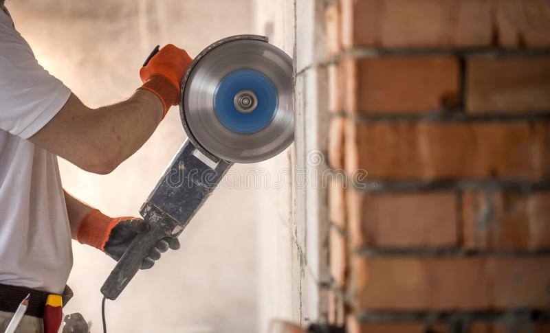 The industrial Builder works with a professional angle grinder to cut bricks and build interior walls. Electrician stock photos