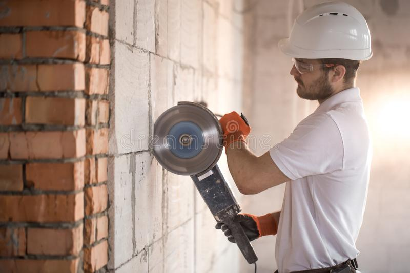 The industrial Builder works with a professional angle grinder to cut bricks and build interior walls. Electrician royalty free stock photography