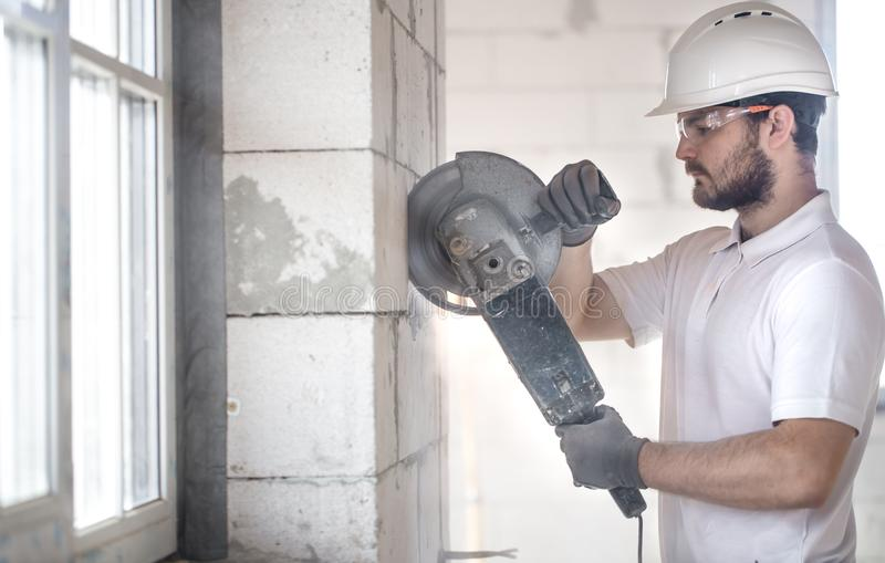 The industrial Builder works with a professional angle grinder to cut bricks and build interior walls. Electrician stock image
