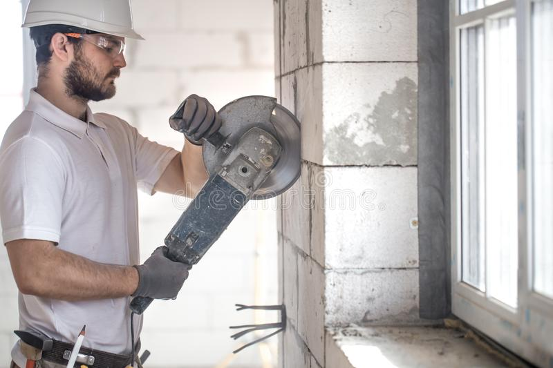 The industrial Builder works with a professional angle grinder to cut bricks and build interior walls. Electrician royalty free stock images