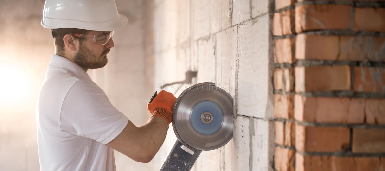 The industrial Builder works with a professional angle grinder to cut bricks and build interior walls. Electrician royalty free stock photos