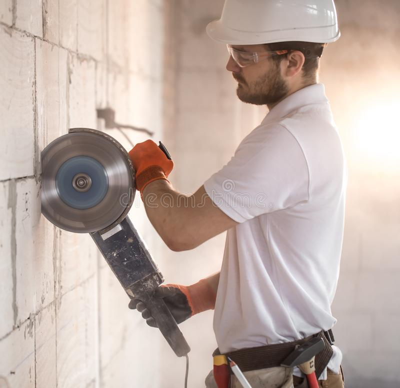 The industrial Builder works with a professional angle grinder to cut bricks and build interior walls. Electrician royalty free stock photo