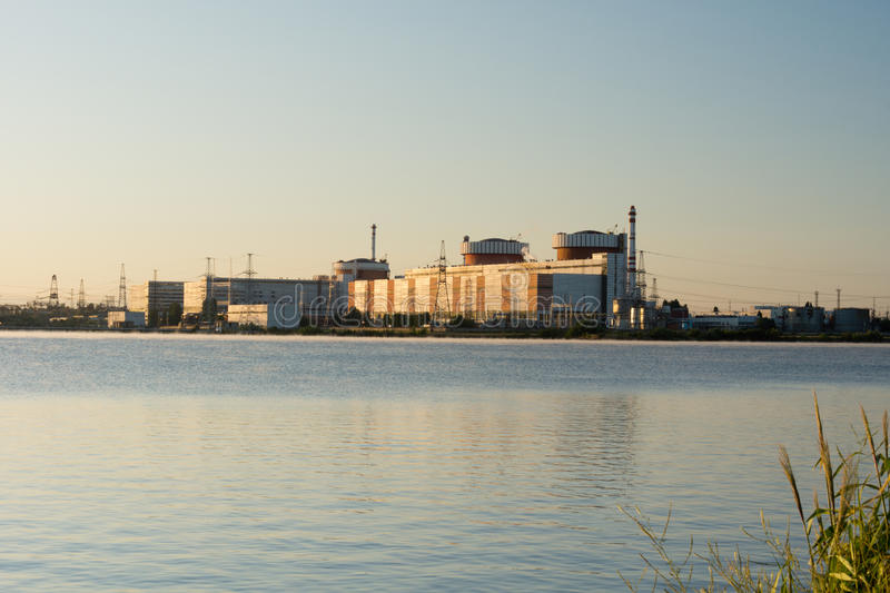 Industrial building on the edge of a waterway. View across the water of an industrial building, refinery, factory, plant or mill on the edge of a waterway with royalty free stock photo