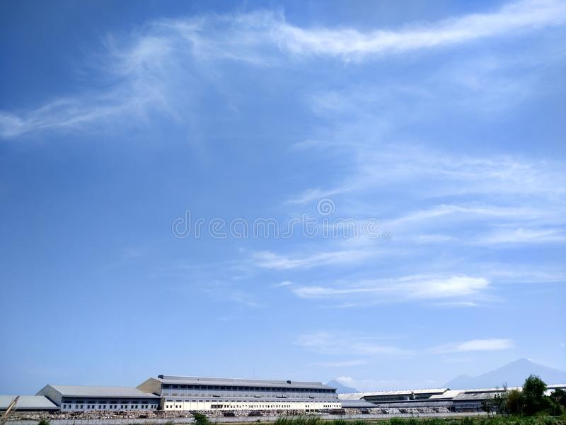 Industrial buildings and blue sky. Landscape view of fields, industrial buildings and blue sky stock photo