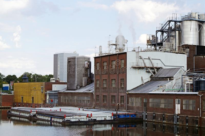 Industrial buildings at a canal. Industrial landscape with industrial buildings at a canal with barges on a sunny day stock photography