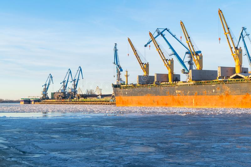 Container cargo freight ship with working crane bridge at shipyard in morning for logistic import and export background royalty free stock photos