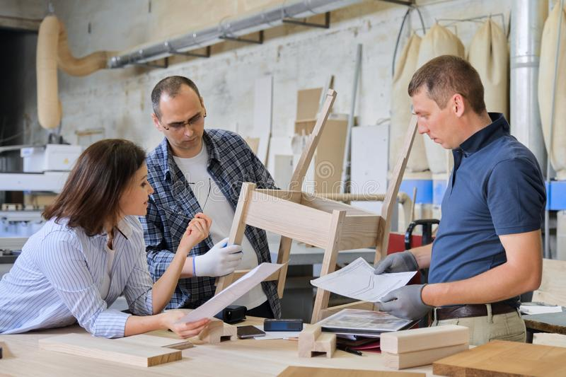 Industrial carpentry workshop, group of working people. Discussing new model of furniture, wooden modern chair stock photos