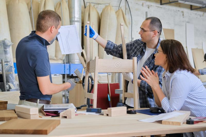 Industrial carpentry workshop, group of working people. Discussing new model of furniture, wooden modern chair royalty free stock photography
