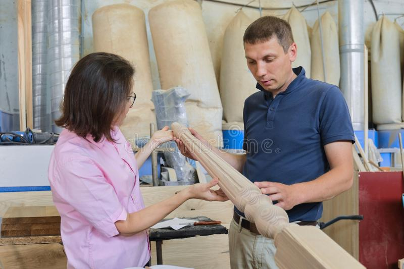 Industrial carpentry workshop, working man and woman. Industrial carpentry workshop, working men and women discussing and developing wooden staircase details royalty free stock image