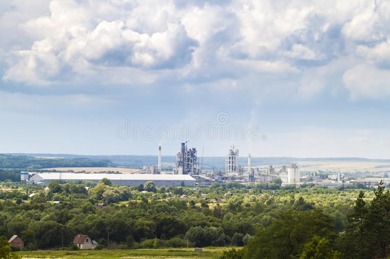 Industrial cement factory with pipes smoking and puffy clouds ab royalty free stock image