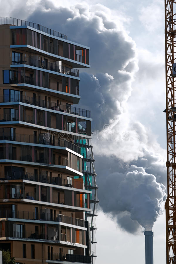 Industrial chimney and modern tower in Paris suburb stock image