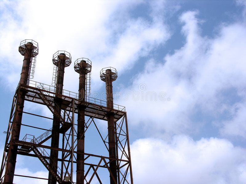 Industrial chimneys. Modern industrial chimneys with blue sky and cloudscape background royalty free stock photos