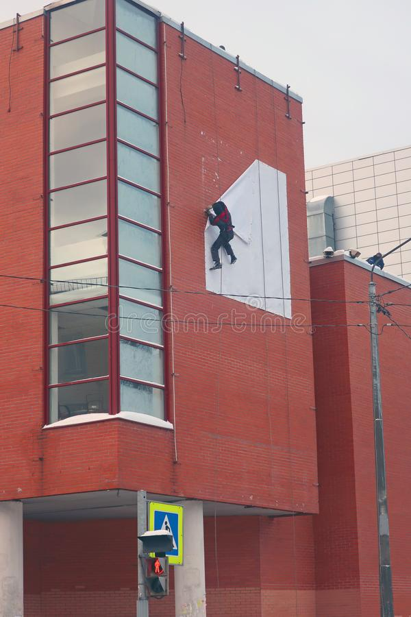 Industrial climber dismantling white banner from red brick wall. Industrial climber dismantling a white banner from a red brick wall high on a building stock images