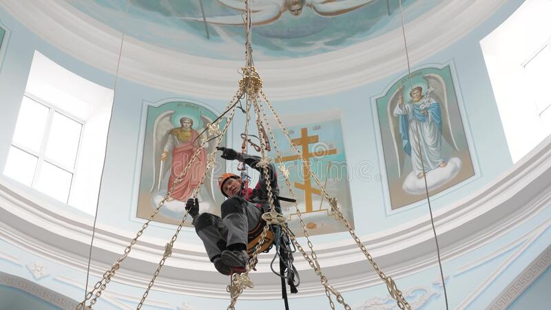 Industrial climber in equipment for high-altitude work working at high altitude in a church building. Climber high royalty free stock photos
