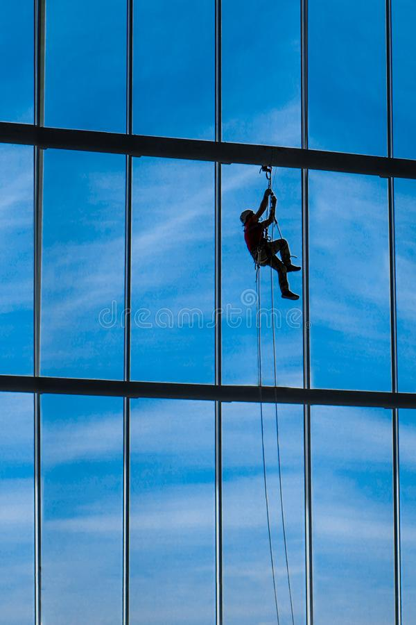 Industrial climber hangs from ropes inside building. Industrial climber hangs from ropes inside shopping center or exhibition hall building against the blue sky stock photography