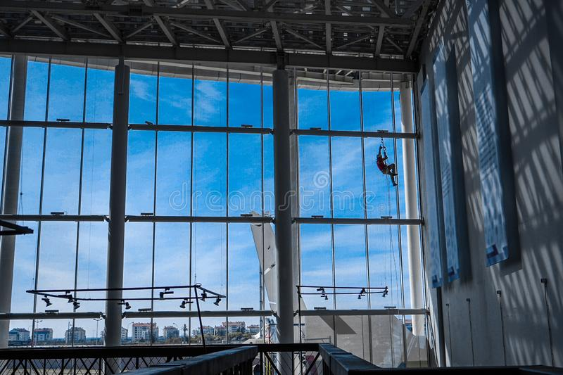 Industrial climber hangs from ropes inside building. Industrial climber hangs from ropes inside shopping center or exhibition hall building against the blue sky royalty free stock photography
