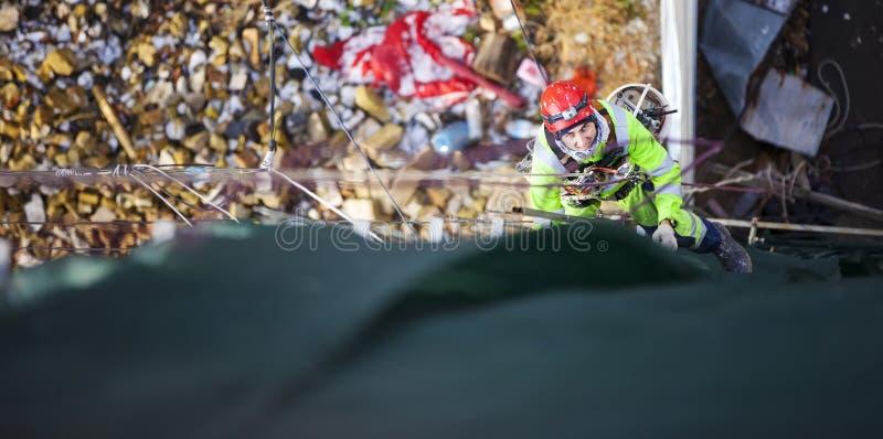 Industrial climber placing exterior advertising stock photo