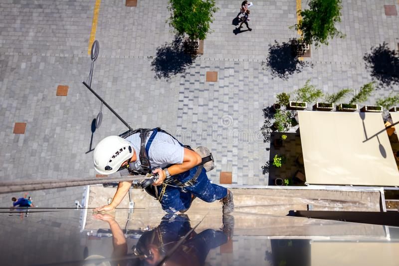 Industrial climber is washing, cleaning facade of a modern office building stock images