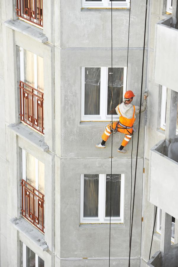 Industrial climber. Builder sealing outside facade building seam joints with insulation mastic royalty free stock photography