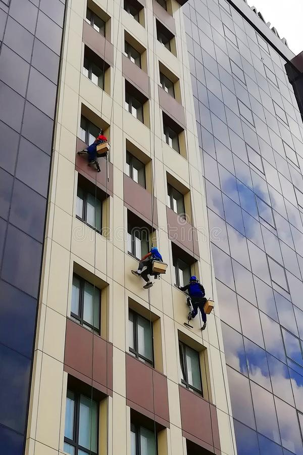 Industrial climbers clean windows of high-rise buildings royalty free stock images