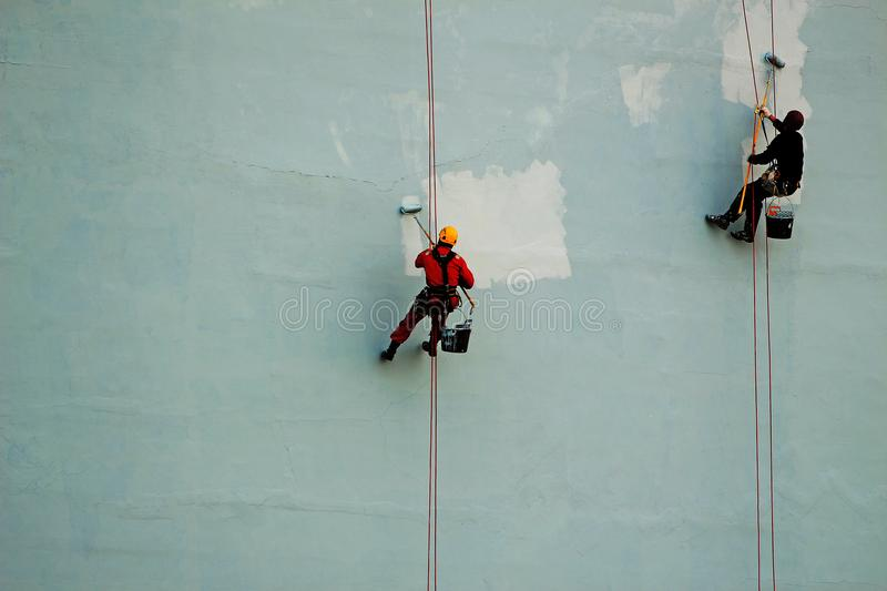 Industrial climbers paint the wall of the building royalty free stock photography