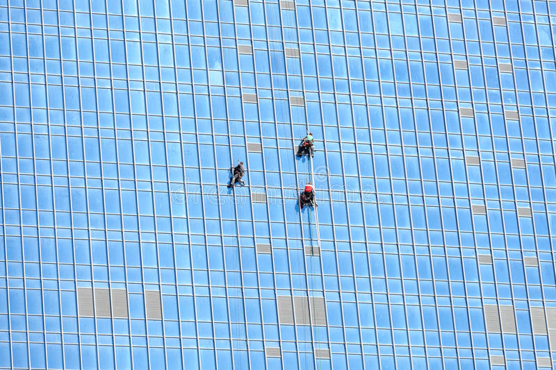 Industrial climbers working on mirror building facade. Blue glass windows royalty free stock image