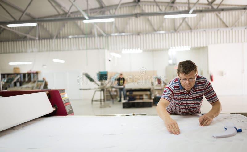 Industrial clothing designer working according to scheme stock photo