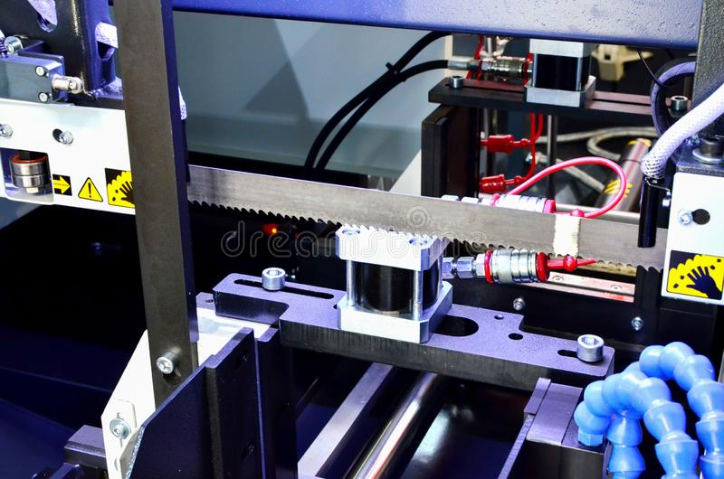Industrial CNC lathe with band saw for cutting metal products. Coolant supplied from plastic tubes. Shooting in real conditions, a little blurry and maybe stock images