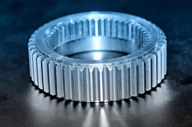 Industrial gear on black background. Blue toned image. Industrial cogwheel, gear with machine teeth on a black background. Blue toned image stock images