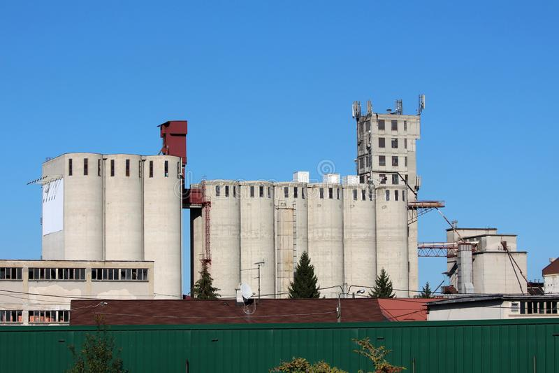 Industrial complex multiple tall concrete storage silos with cell phone antennas and transmitters on top surrounded with dark stock photos