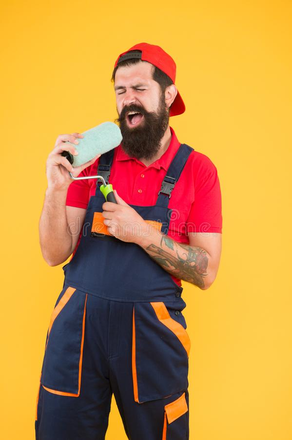 Industrial concept. creative repair concept. bearded man singing in roller tool. hipster builder in cap yellow stock photography