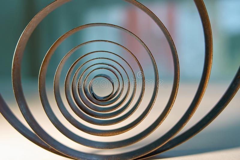 Industrial concept. Old metal spiral on a window background. Spirally expanding royalty free stock image