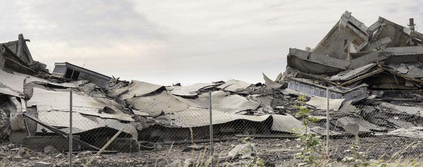 Industrial concrete building destructed by strike. Disaster scene full of debris, dust and crashed buildings.  stock images