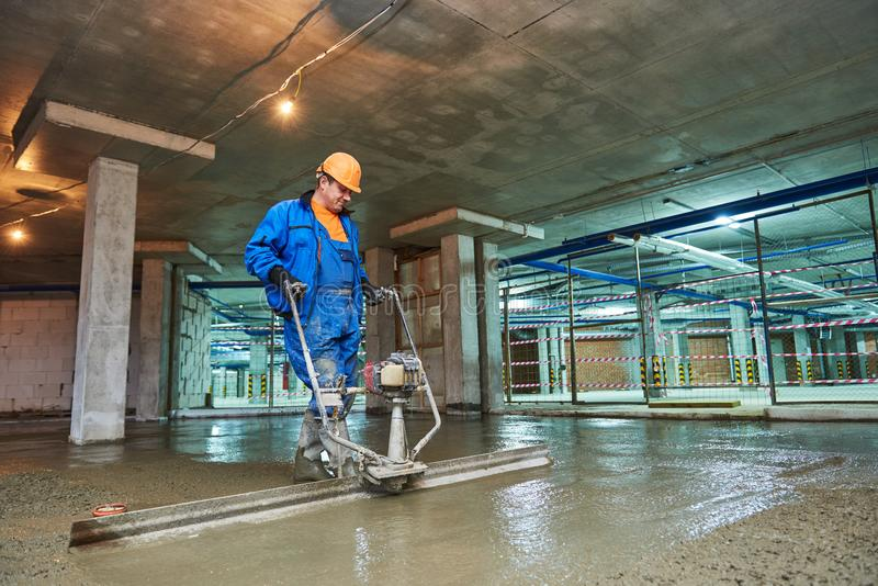 Concrete floor construction. Worker with screeder royalty free stock photos
