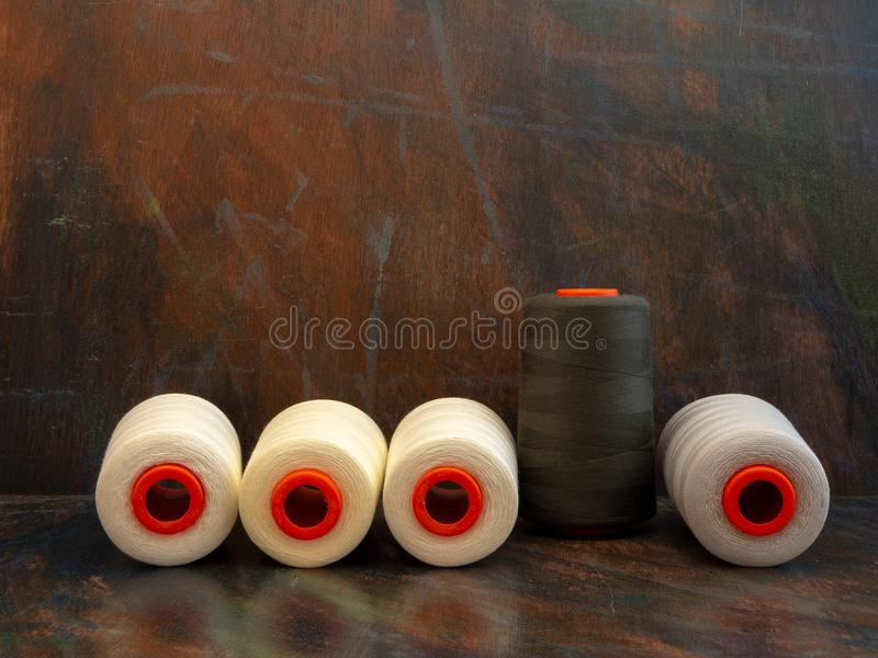 Industrial cones of sewing threads on a dark background. Front view studio shot. royalty free stock photography