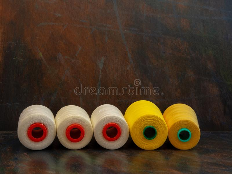 Industrial cones of sewing threads laying on a dark background. Front view studio shot. stock image